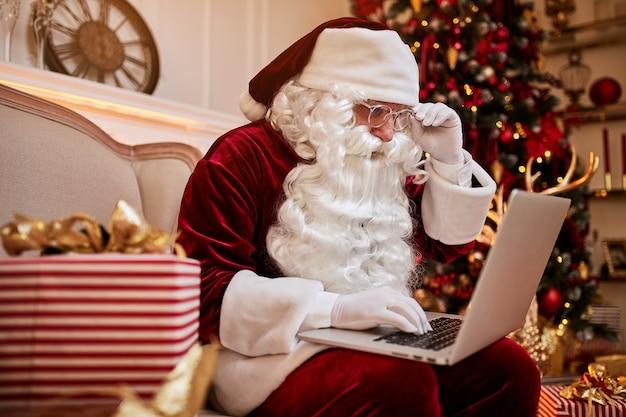 Babbo natale seduto a casa sua e leggendo e-mail sul laptop con richieste di natale o lista dei desideri vicino al camino e albero con regali.