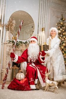 Babbo natale e snegurochka in posa vicino all'albero del nuovo anno