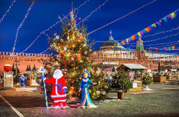 Babbo natale e fanciulla di neve all'albero di capodanno sulla piazza rossa a mosca in una notte d'inverno