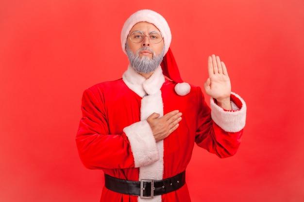Babbo natale in piedi alzando la mano e dicendo giurare, fare giuramento di fedeltà, giurare fedeltà.