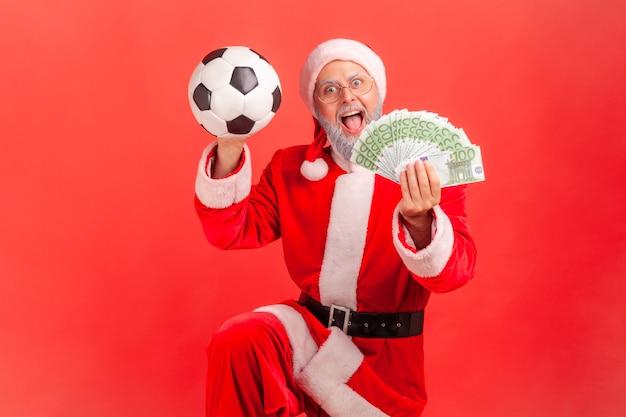 Babbo natale in piedi con banconote in euro e pallone da calcio, felice di scommettere e vincere,
