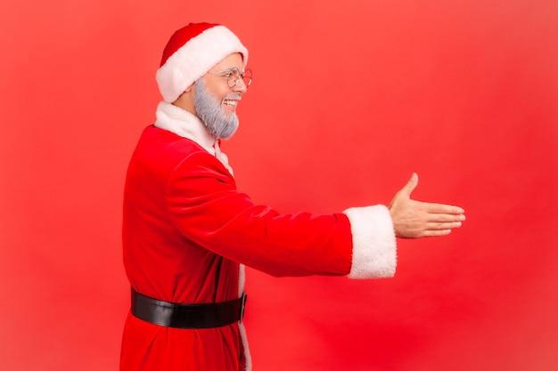 Babbo natale allungando la mano accogliendo gli ospiti alla festa di capodanno, ospitalità.