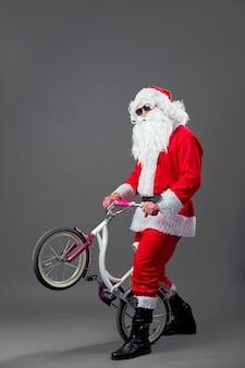 Babbo natale in occhiali da sole e cuffie mette la bici sulla ruota posteriore sullo sfondo bianco. .