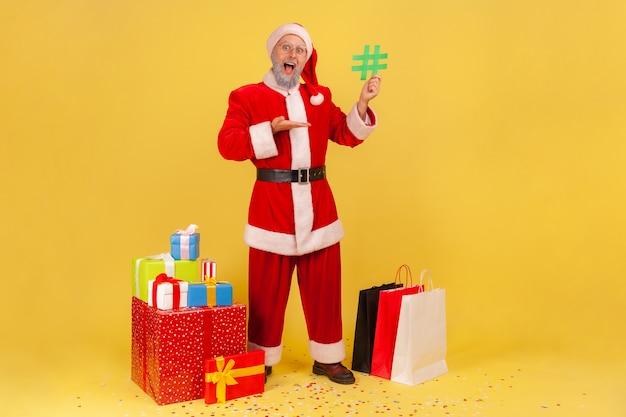 Babbo natale circondato da regali di natale, indicando l'hashtag verde nelle sue mani.