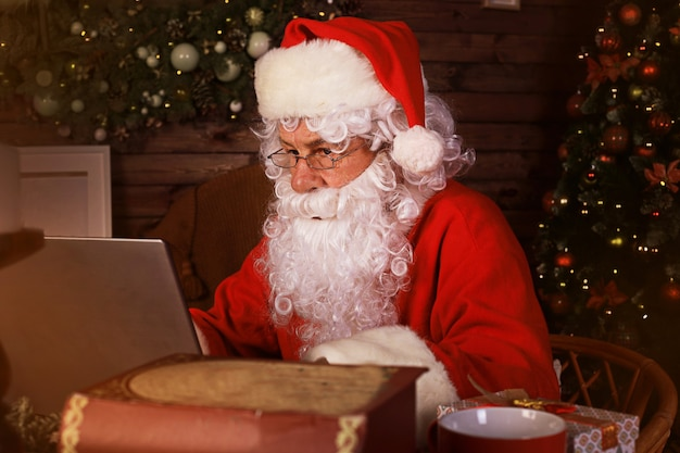 Babbo natale che utilizza il computer portatile seduto in una stanza accogliente vicino al camino.