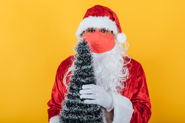 Babbo natale che indossa una maschera rossa e tiene in mano un albero di natale, sul giallo