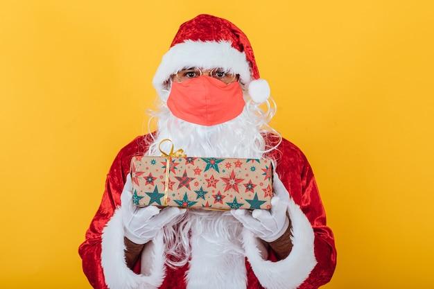 Babbo natale indossa una maschera rossa e tiene un regalo, su giallo