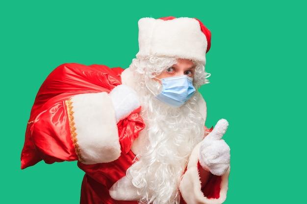Babbo natale indossa una maschera facciale di carta a causa del covid-19. il coronavirus è pericoloso ed è diffuso in tutto il mondo. stai al sicuro e indossa una maschera. isolato. spazio per il testo.
