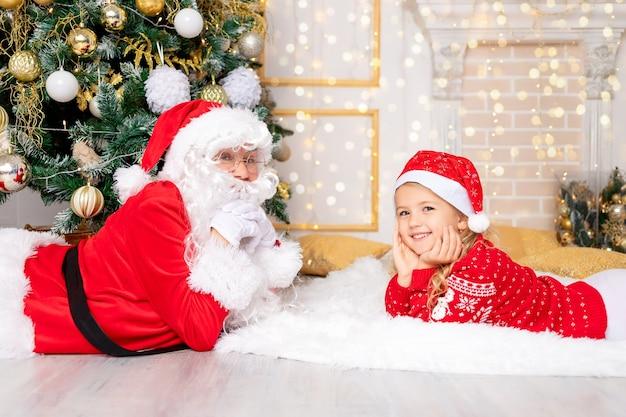 Babbo natale con una bambina all'albero di natale, capodanno e concetto di natale
