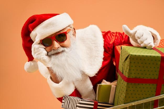 Babbo natale con la barba in occhiali da sole rossi mostrando segno ok