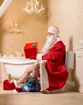 Babbo natale con i pantaloni abbassati seduto sul water e tenendo in mano la confezione regalo. umorismo natalizio