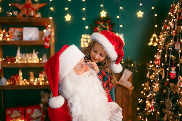 Babbo natale con una bambina carina gioca nella stanza. periodo natalizio.