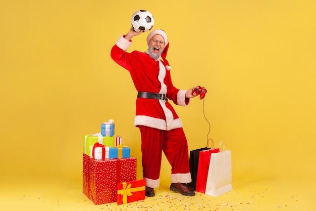 Babbo natale con pallone da calcio, tenendo il joystick, celebrando la vittoria nel videogioco di calcio.