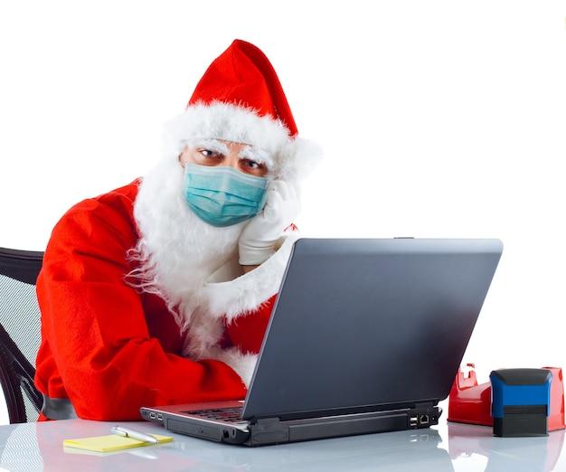 Babbo natale con mascherina chirurgica funziona con il computer portatile