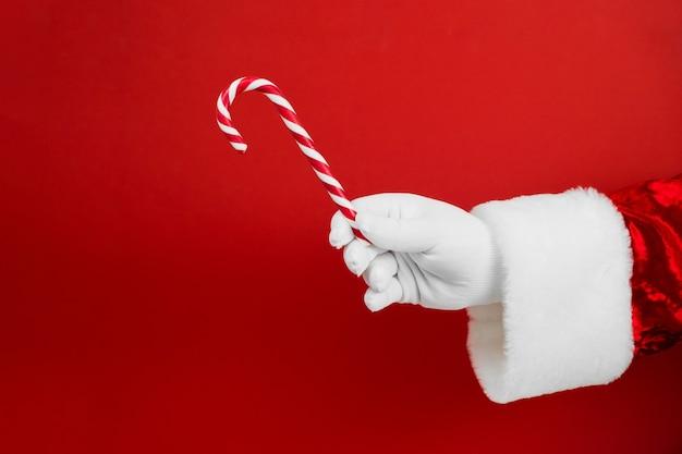 Mano della santa con il bastoncino di zucchero di natale sul rosso