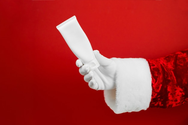 Mano di babbo natale con tubo cosmetico. mock up per crema, scrab, maschera.