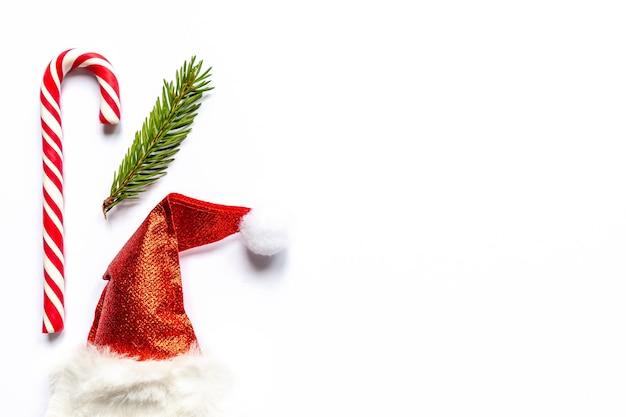 Cappello da babbo natale e bastoncino di zucchero e ramo di abete su sfondo bianco creativo capodanno piatto disteso con poliziotto...