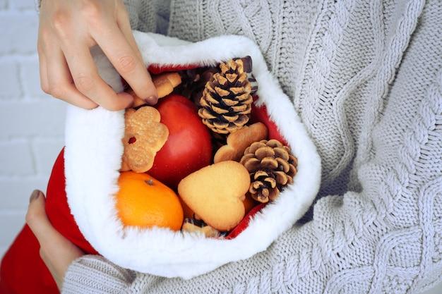 Cappello da babbo natale pieno di regali di natale nelle mani di una donna