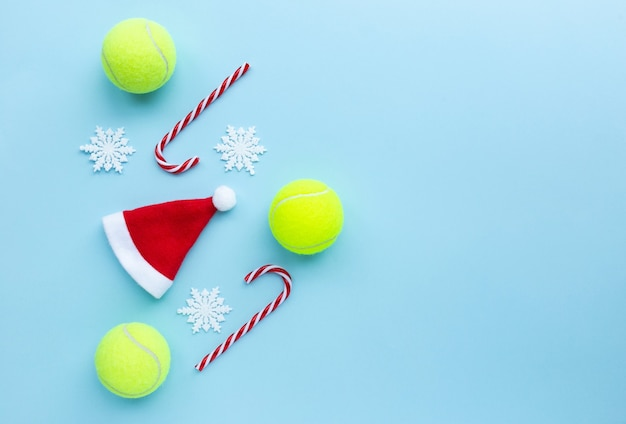 Cappello da babbo natale, palline da tennis, bastoncini di zucchero e fiocchi di neve su sfondo blu