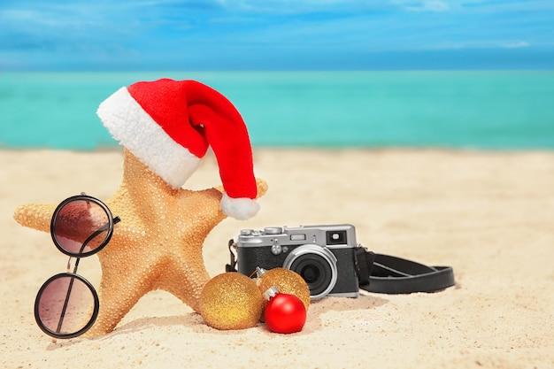 Cappello da babbo natale con stella marina, macchina fotografica e occhiali da sole sulla spiaggia. concetto di vacanze di natale