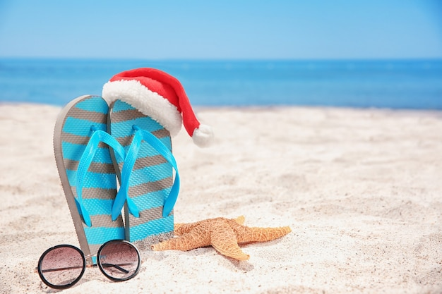 Cappello da babbo natale con stella marina, infradito e occhiali da sole sulla spiaggia. concetto di vacanze di natale