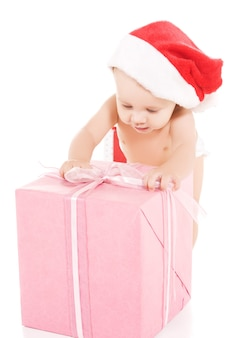 Santa helper bambino con regali di natale sul muro bianco