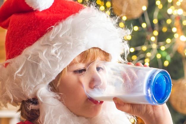Biscotto della holding della santa e bicchiere di latte sull'albero di natale. biscotti per bambino di babbo natale