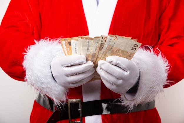 Santa che tiene cinquanta euro fatture isolate su priorità bassa bianca. moneta europea