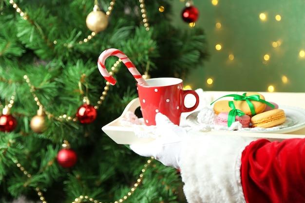 Babbo natale che tiene tazza e piatto con i biscotti in mano, su sfondo luminoso