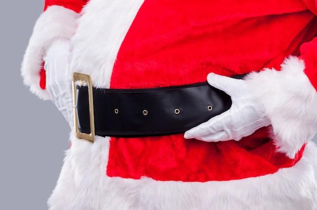 Babbo natale è qui! vista laterale ravvicinata del babbo natale tradizionale che si regola la cintura mentre si trova su uno sfondo grigio