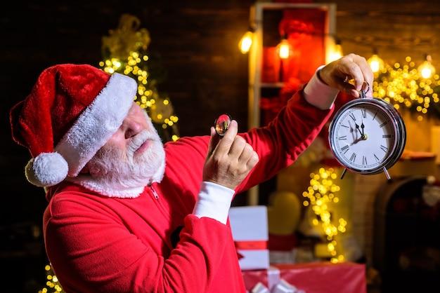 Babbo natale che guarda attraverso la lente d'ingrandimento l'orologio di natale uomo barbuto con cappello santa tiene l'ingrandimento