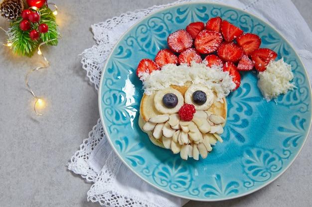Pancake di babbo natale con fragole per colazione per bambini