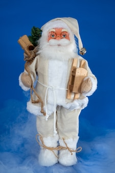 Bambola pupazzo di babbo natale con slitta in legno contro blu con fumo nebbioso