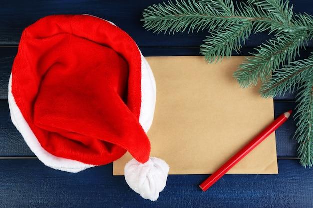 Cappello di babbo natale rosso con ramo di abete, foglio di carta e matita