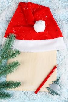 Cappello rosso di babbo natale con ramo di abete, foglio di carta, matita e fiocchi di neve su superficie in legno colorato