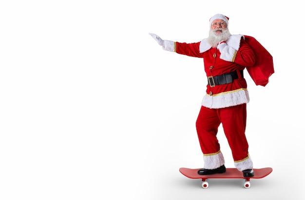 Babbo natale in sella a uno skateboard o longboard e con in mano una borsa piena di regali su sfondo bianco.