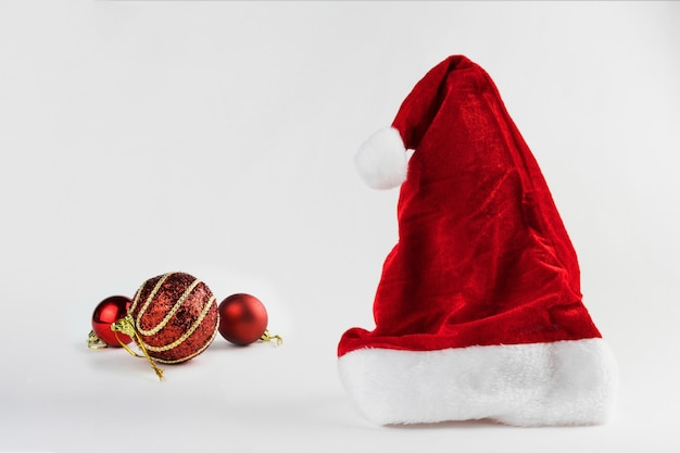 Cappello e palline di babbo natale isolati su sfondo bianco. ornamento di natale. messa a fuoco selettiva.