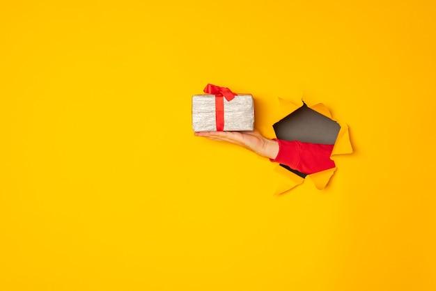 La mano di babbo natale che tiene una scatola con un regalo sullo sfondo giallo del foro