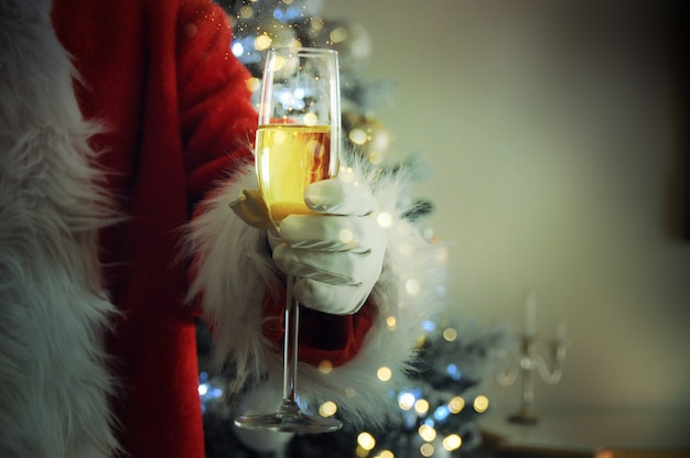 La mano di babbo natale con lo champagne