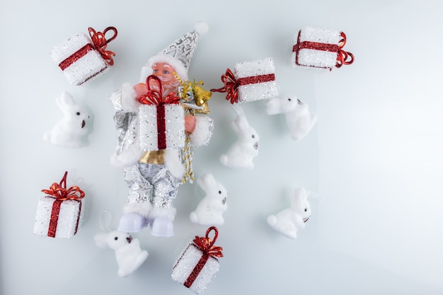 Giocattolo di babbo natale in abiti bianchi e decorazioni natalizie sull'albero di natale