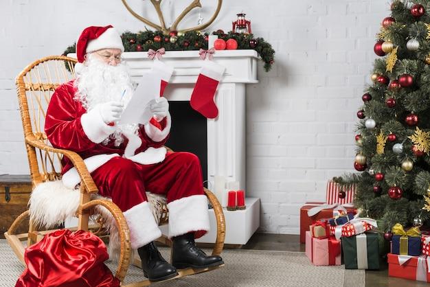 Santa che si siede sulla sedia a dondolo vicino all'albero di natale