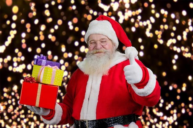Santa con i regali che mostrano pollice in su.