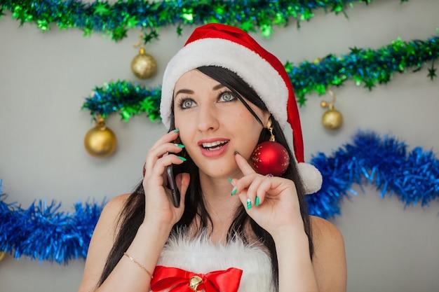 Aiutante sexy di babbo natale bruna appassionata in un costume da elfo con un telefono in mano
