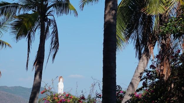 Sanya, hainan, cina - paesaggio con palme tropicali e dea della misericordia situata nel mare contro il cielo blu nel centro culturale buddista di nanshan