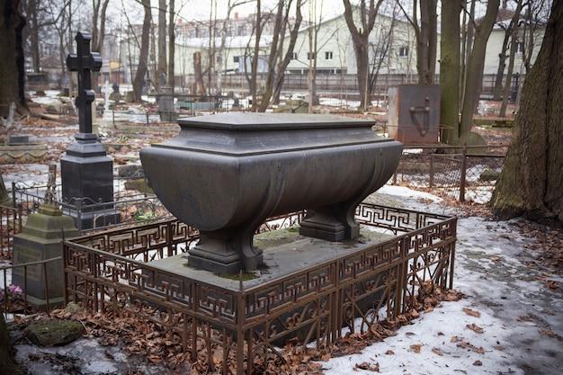 Sarcofago su piedistallo di pietra nel mezzo del cimitero invernale - cimitero luterano di smolenskoe, russia, san pietroburgo, marzo 2021