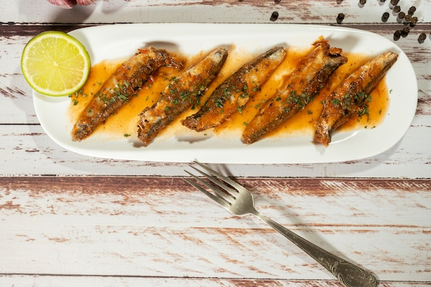 Sardine in salsa di pomodoro e prezzemolo servite in un piccolo piatto bianco. vista dall'alto, copia testo.