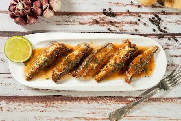 Sardine in salsa di pomodoro e prezzemolo servite in un piccolo piatto bianco. vista dall'alto,