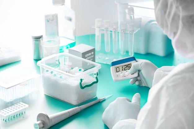 Kit diagnostico per acidi nucleici sars-cov-2. l'epidemiologo in tuta protettiva, maschera e occhiali esegue e analizza i risultati dei test pcr per diagnosticare il virus sars-ncov-2, causa della polmonite virale covid-19.