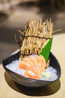 Il sashimi in ciotola nera consiste del salmone (causa) messo su ghiaccio - concetto giapponese dell'alimento.