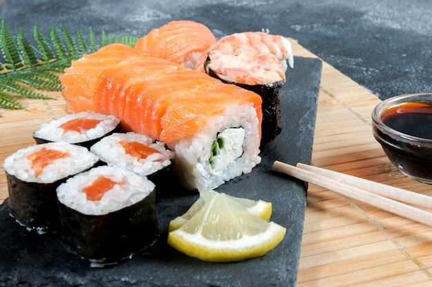 Il sashimi rotola su una lastra di pietra nera. primo piano di sushi con bacchette e soia